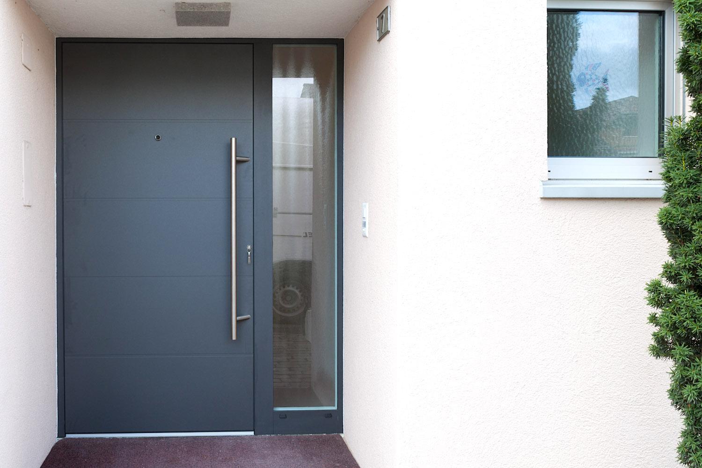 EFH in Fislisbach - Aluminium-Eingangstür mit elektronischem Türspion und seitlicher FestverglasungVerglasung: Verbundsicherheitsglas Chinchilla