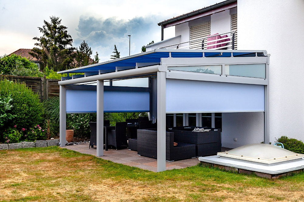 Terrassendach in 8962 Bergdietikon (07/2018) - Ausführung:Aluminium-Terrassendach VERANDA K mit festverglasten, schrägen Oberlichtern. Ausführung mit 3 StützenBreite x Tiefe: 5600 mm x 3900 mmVerglasung: Verbundsicherheitsglas 10 mmBeschattung: WAREMA Aufdachmarkise W20, 2 Stück WAREMA Senkrechtmarkisen mit ZIP-FührungSonderausstattung: LED-Beleuchtung in den Dachsparren