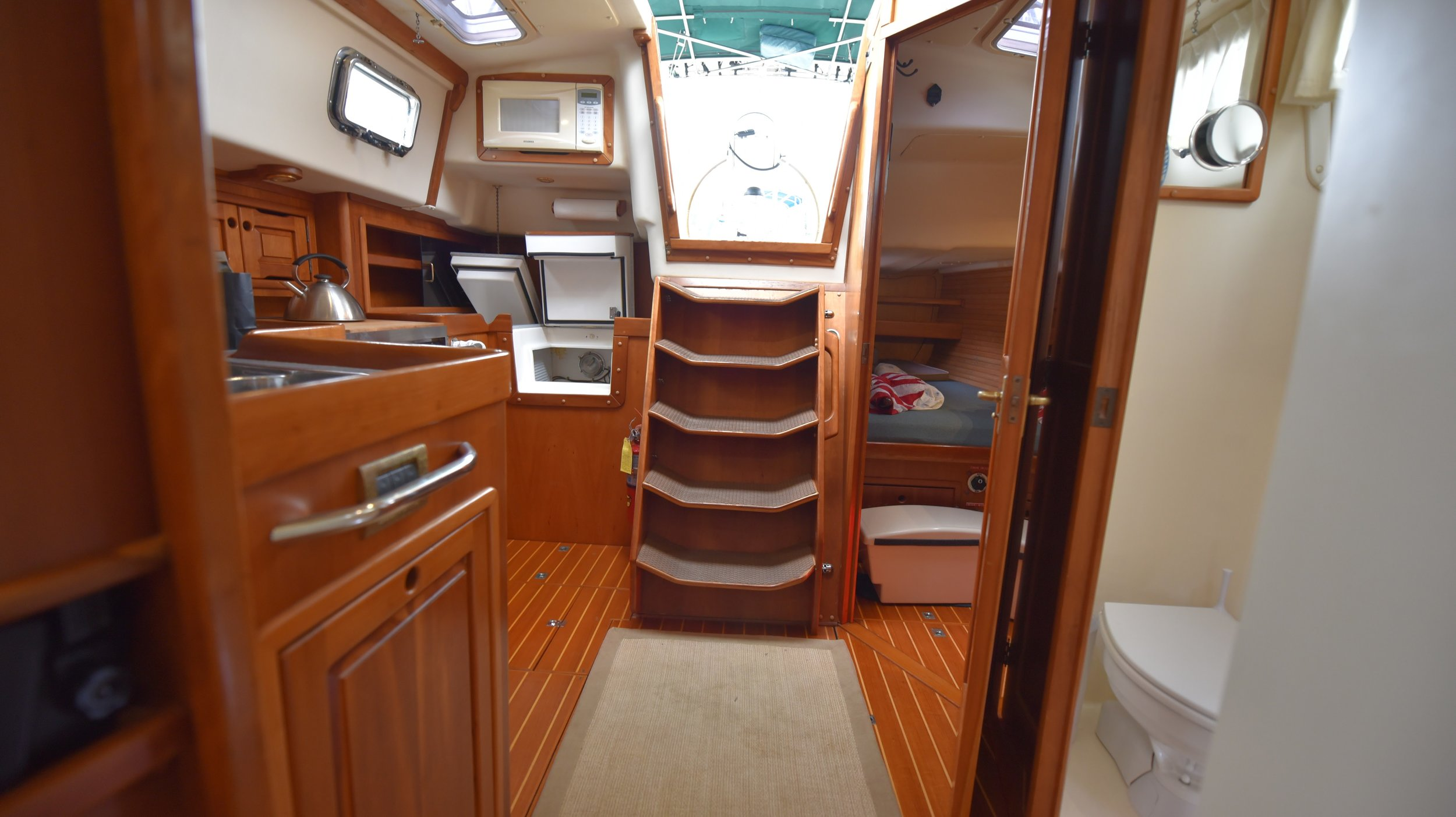 Looking aft from the salon: head to port and Rev's berth aft of the head. Kitchen on the starboard side.