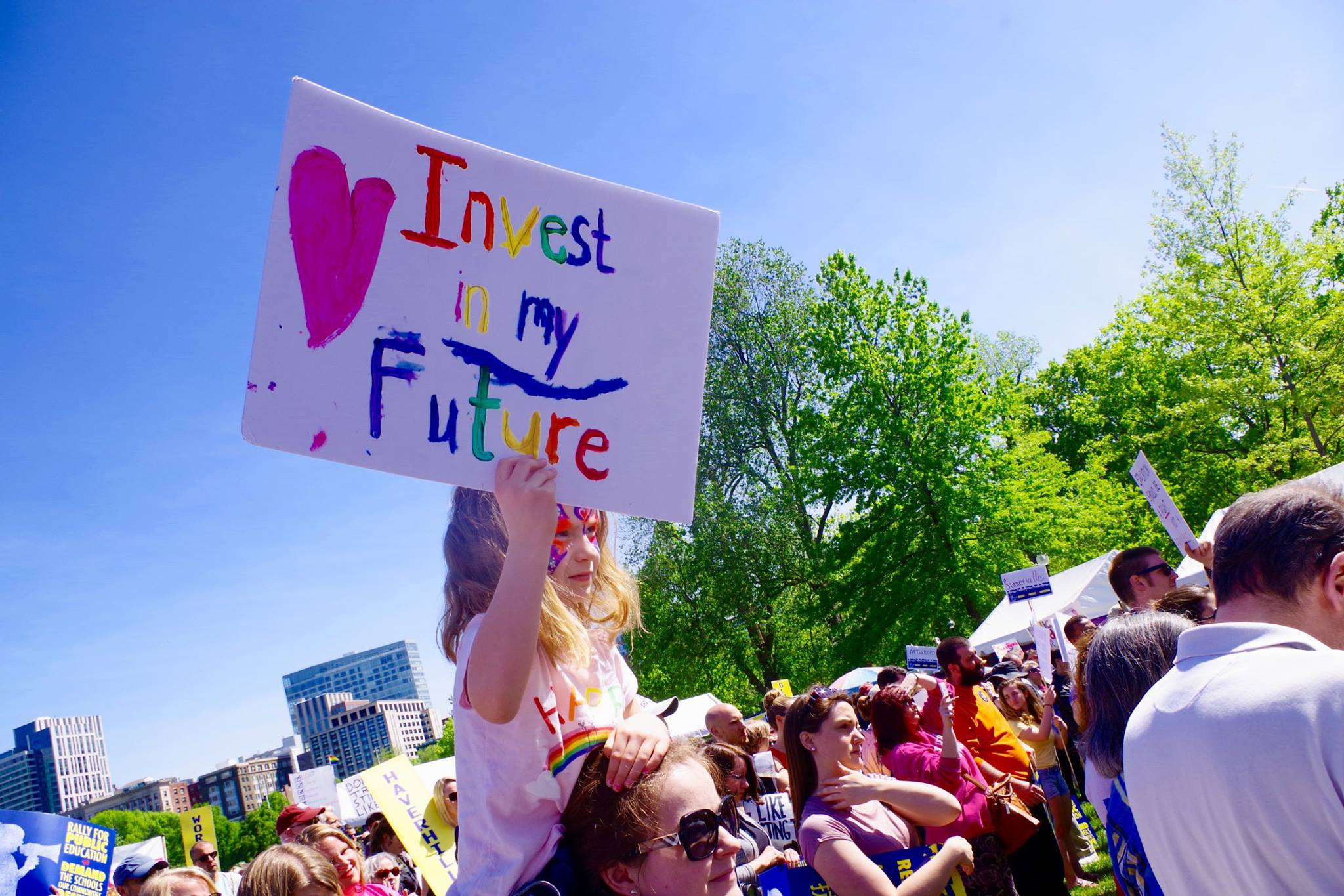 """A child holds a sign that reads """"Invest in My Future"""" at the rally. (Dave Madeloni)"""