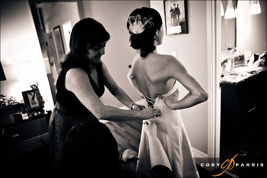 bride getting dress tied by seattle weddding photographers cory parris