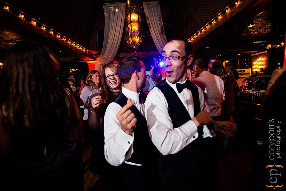 A couple of groomsmen dancing
