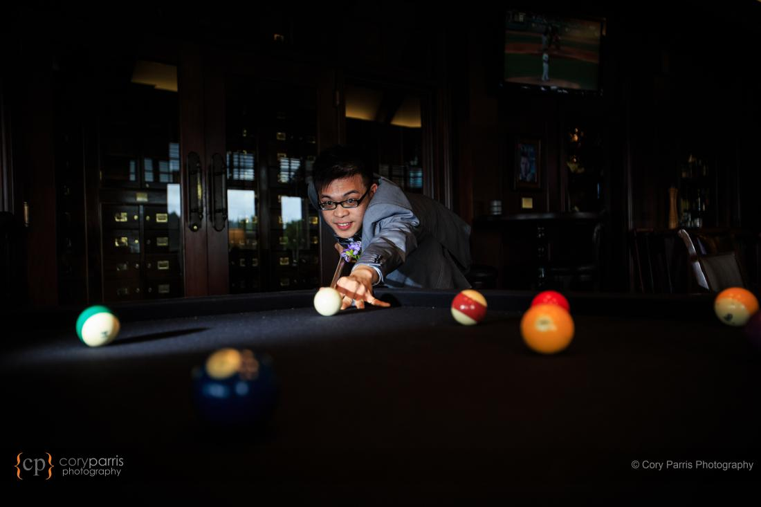 Groom playing pool in the Wooly Toad, a bar on site at Newcastle