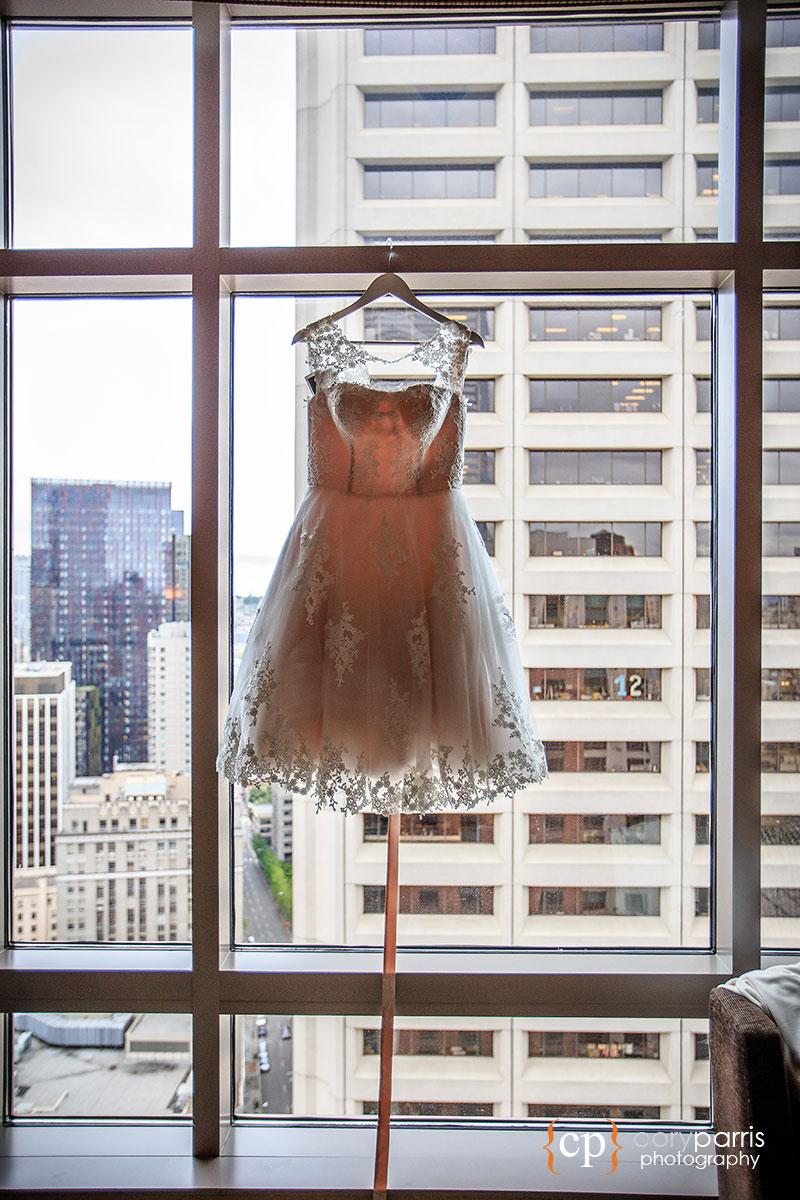 Short wedding dress hanging in a window