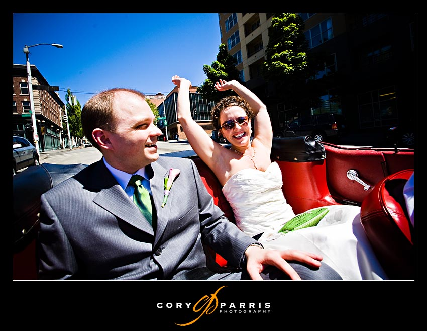 bride and groom in seattle riding in the back of a convertible
