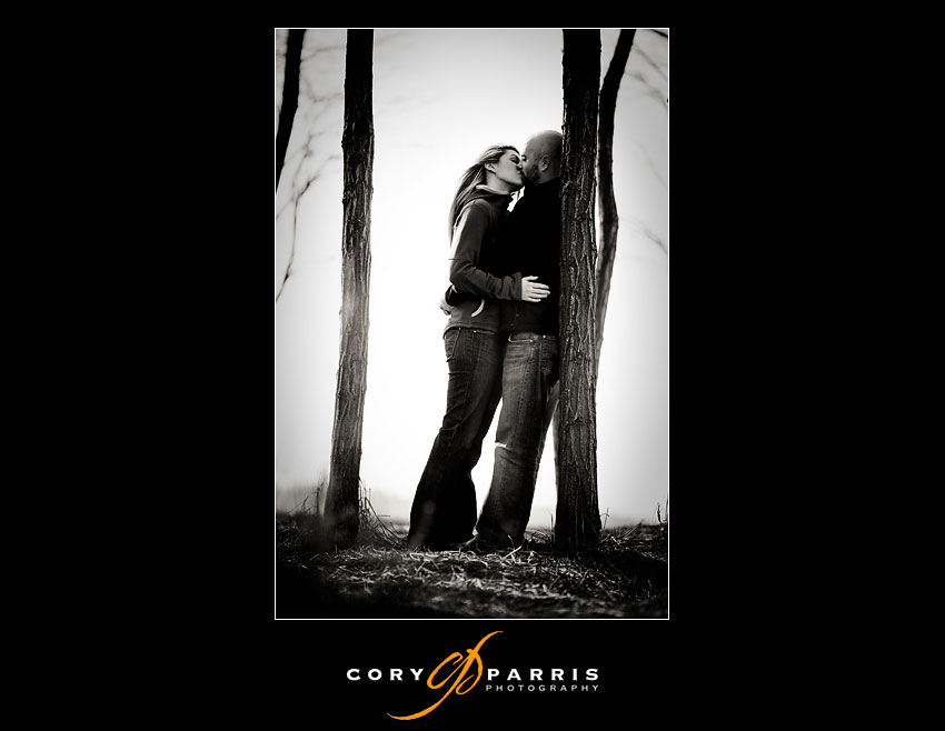 couple kissing by a winter tree