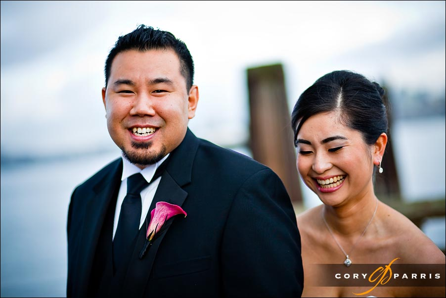 bride and groom laughing on a dock in Seattle
