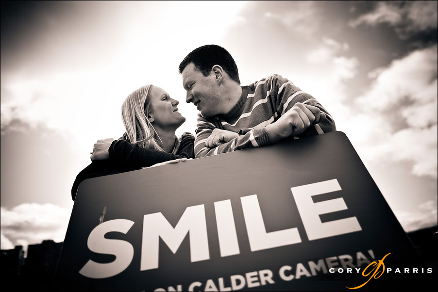 couple looking at each other over a sign that says smile