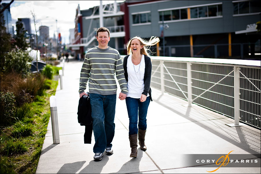 couple laughing as they walk on the seattle waterfront