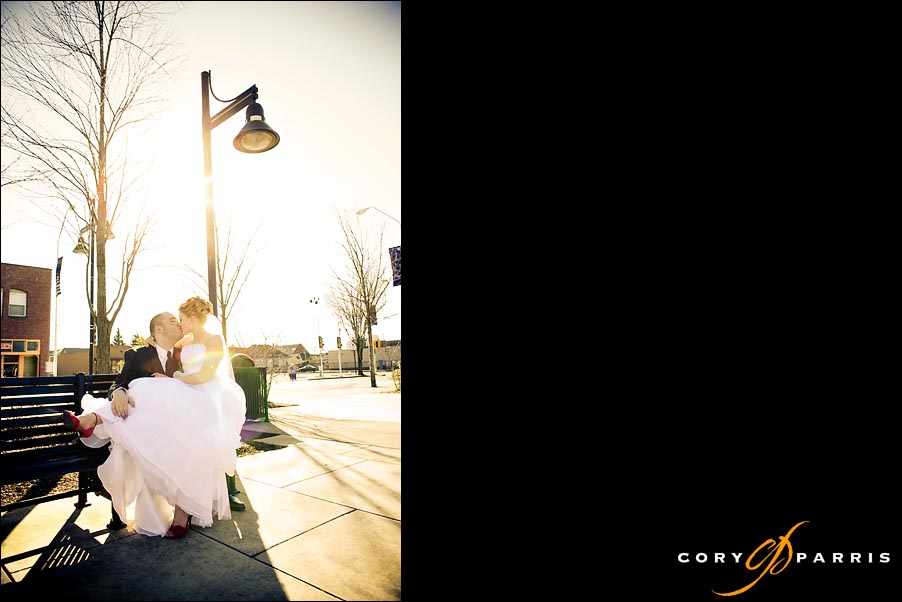 portrait of bride and groom on a park bench with lens flare