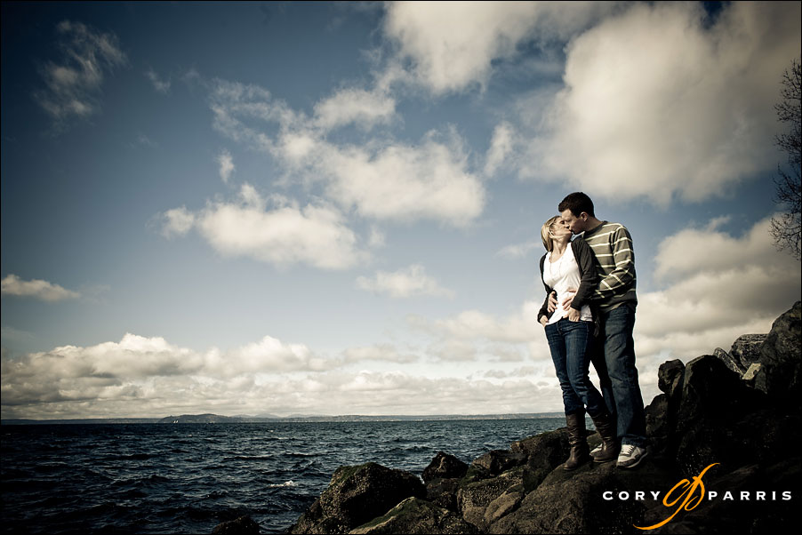 couple kissing on the rocks at the seattle waterfront