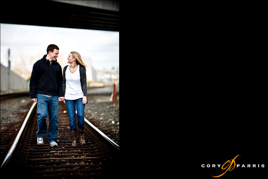 couple walking on the railroad tracks underneath the olympic sculpture park in seattle