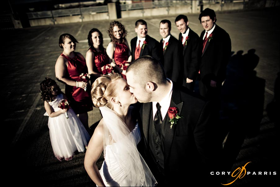 bride and groom kissing in front of their wedding party by seattle wedding photographer cory parris