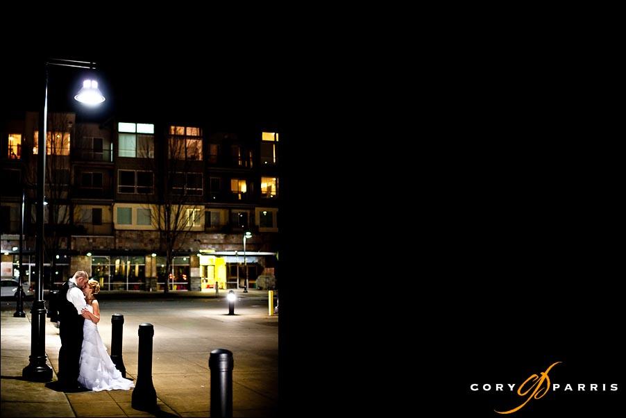 bride and groom standing under a street lamp in renton