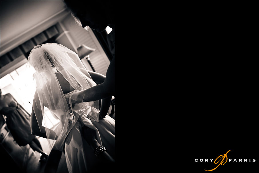 bride getting zipped and buttoned by wedding photojournalist in seattle cory parris