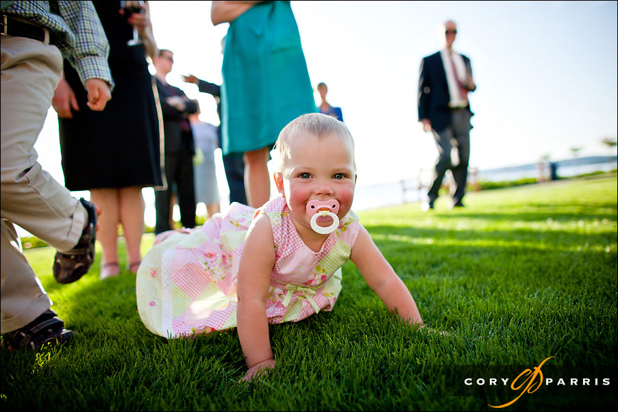 baby crawling in the grass at a wedding reception by seattle wedding photographer cory parris