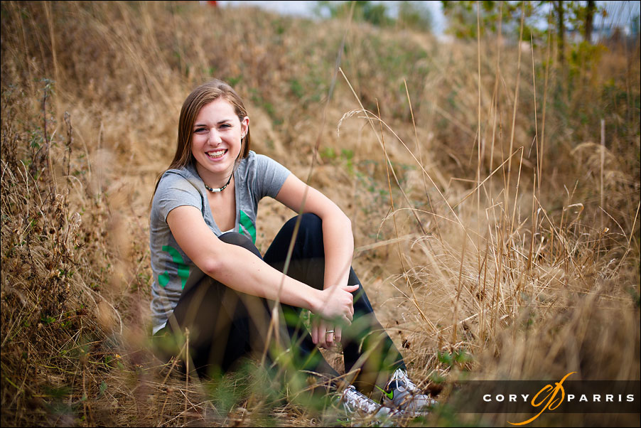 senior girl sitting in a field by seattle portrait photographer cory parris