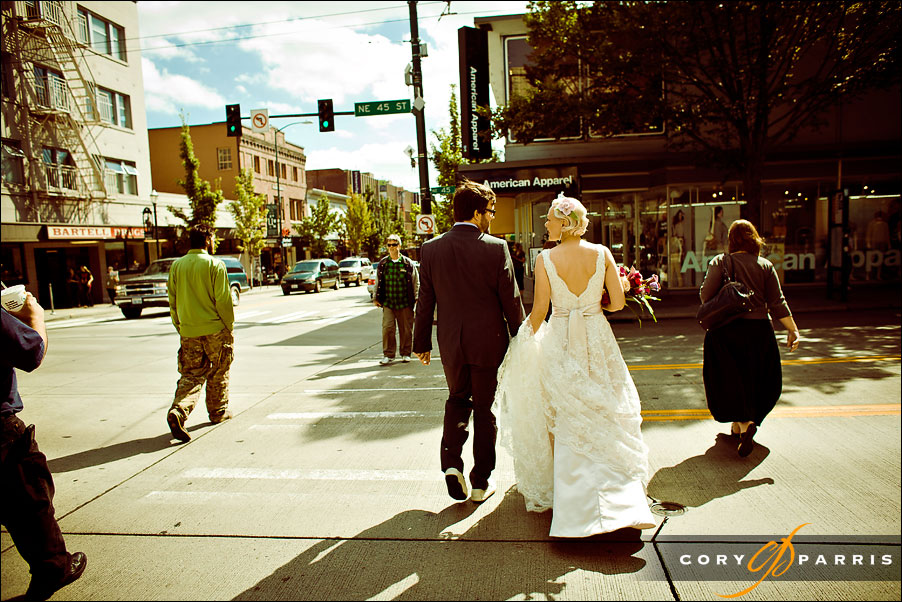 bride and groom crossing the street near the university of washington by seattle wedding photojournalist cory parris