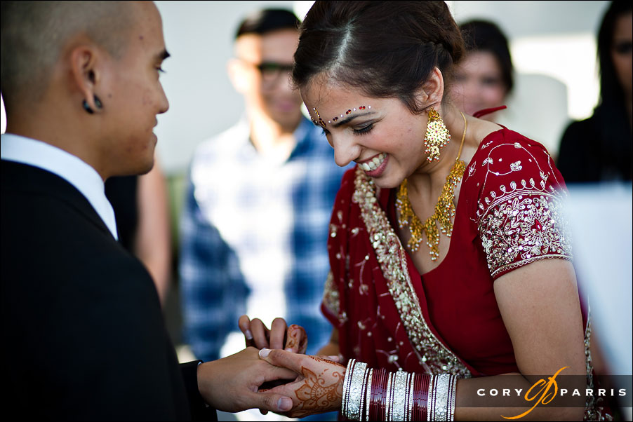 bride laughing as she puts the ring on the groom's finger by seattle wedding photographer cory parris