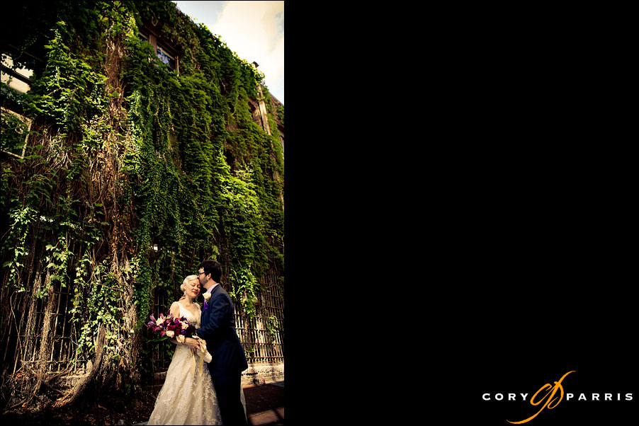 bride and groom kissing in front of an ivy-covered wall by seattle wedding photographer cory parris