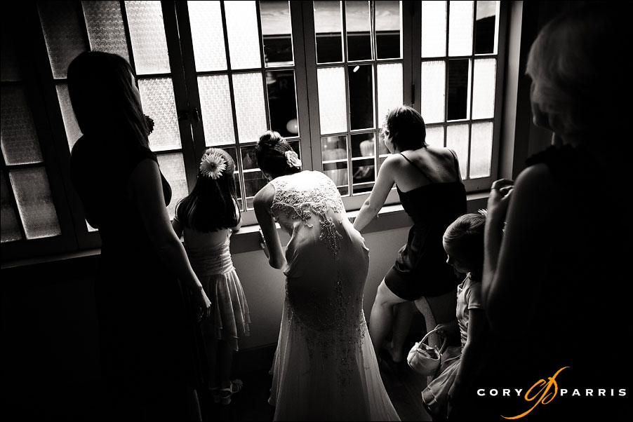 bride peaking through the windows at the wedding guests by wedding photojournalist in seattle cory parris