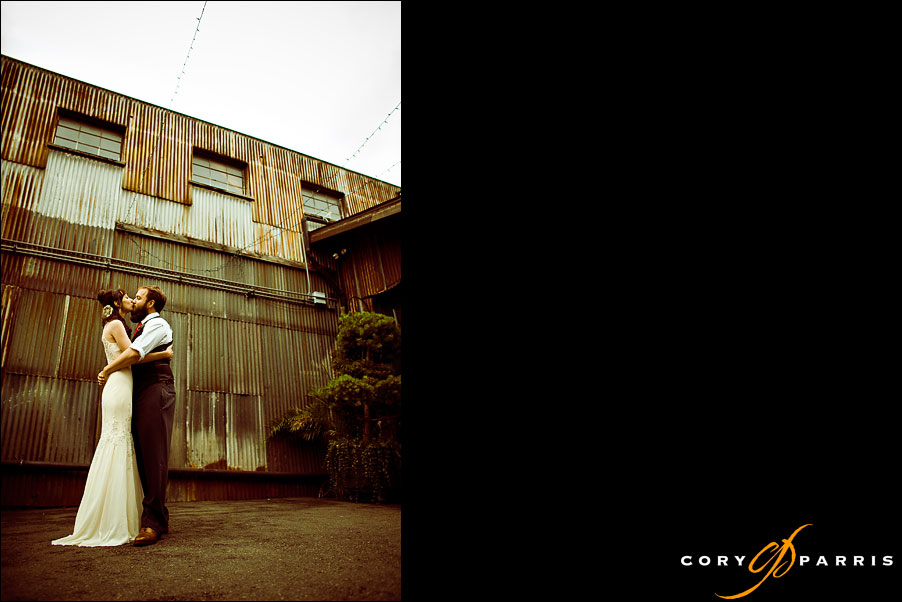 bride and groom in front of rusty wall by seattle wedding photographer cory parris