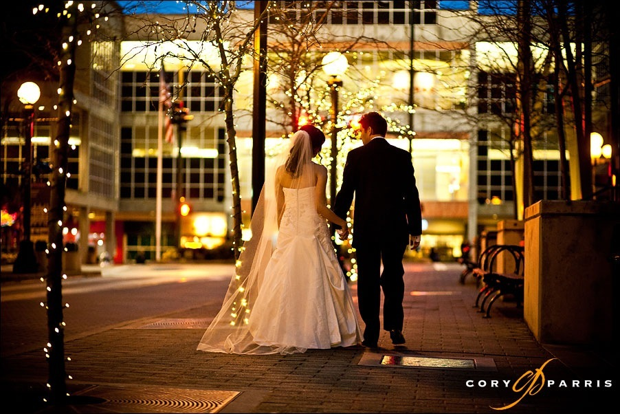 bride and goom walking in the lights in downtown bellevue by photographer cory parris