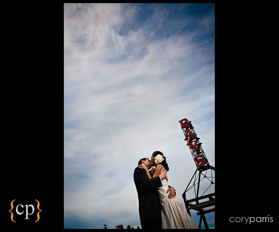 bride and groom kissing in front of the ray's sign in seattle