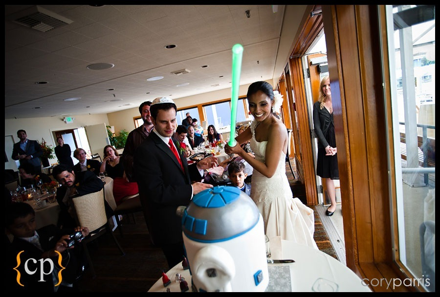 cutting the r2-d2 wedding cake with a lightsaber