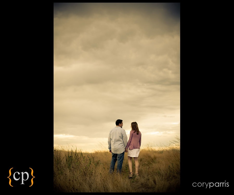 couple walking in a field on a cloudy day by seattle portrait photographer cory parris