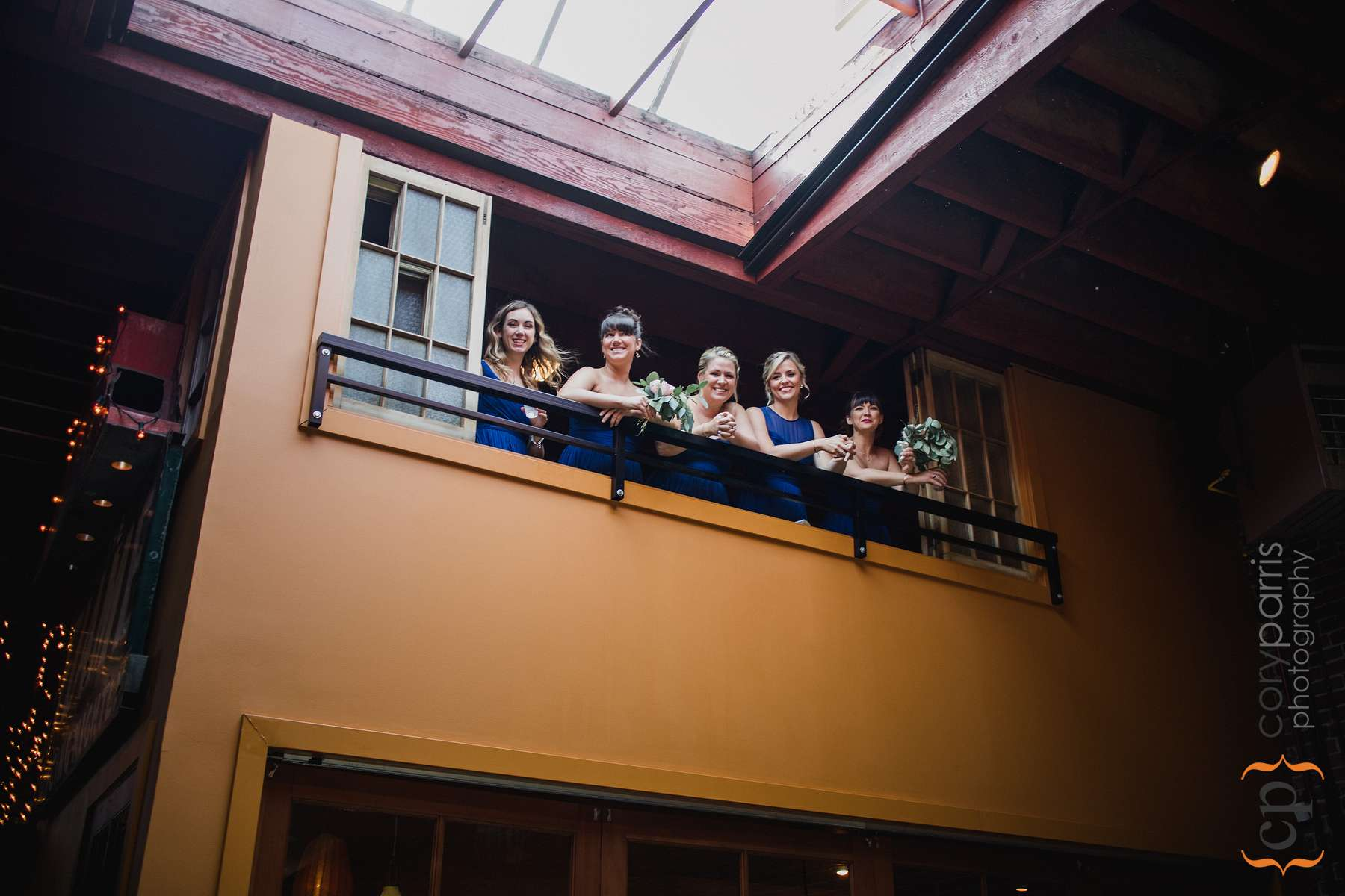 Bridesmaids looking down from the balcony. Photo by Alyssa Parris