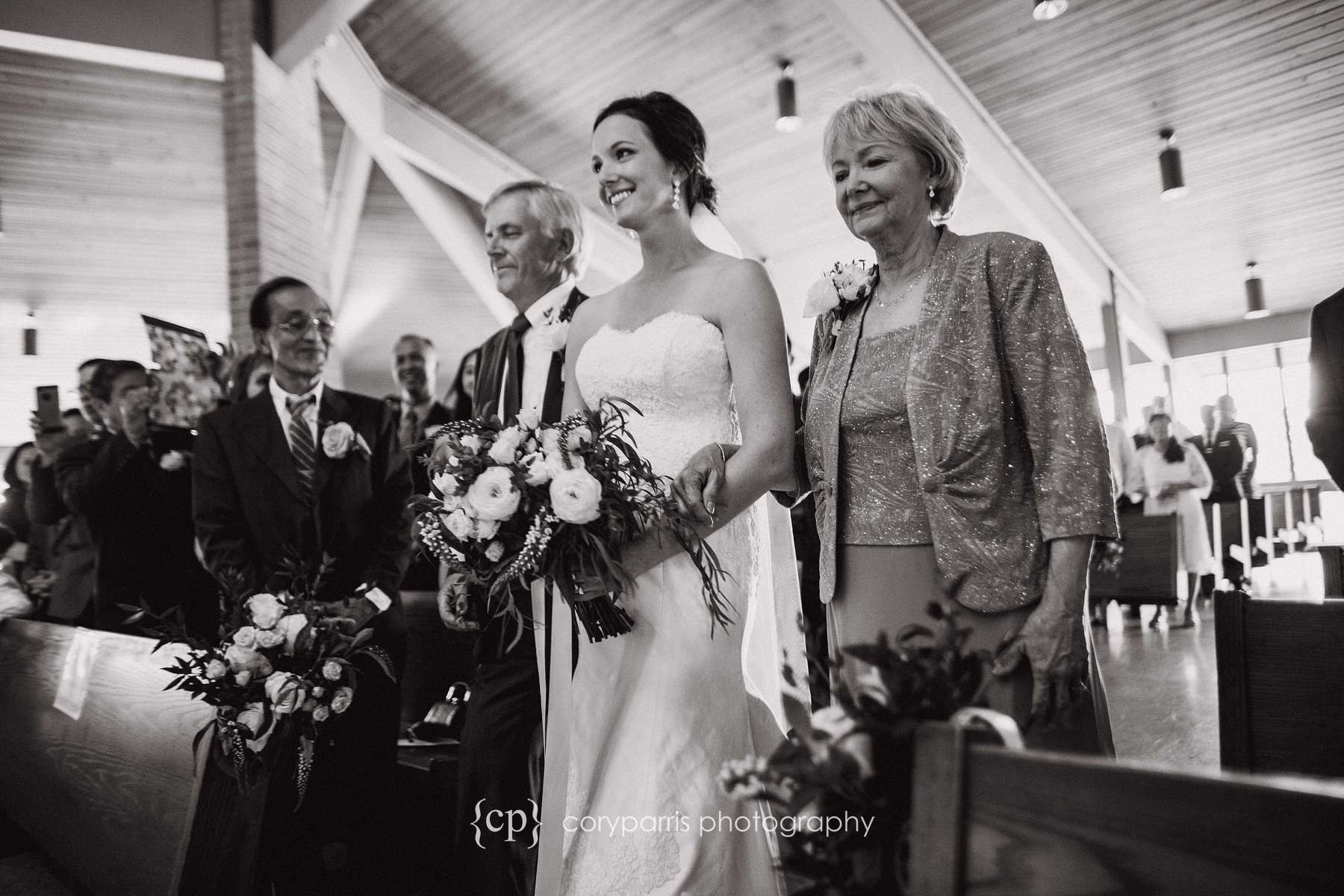 Angie walking down the aisle with her parents before the wedding.