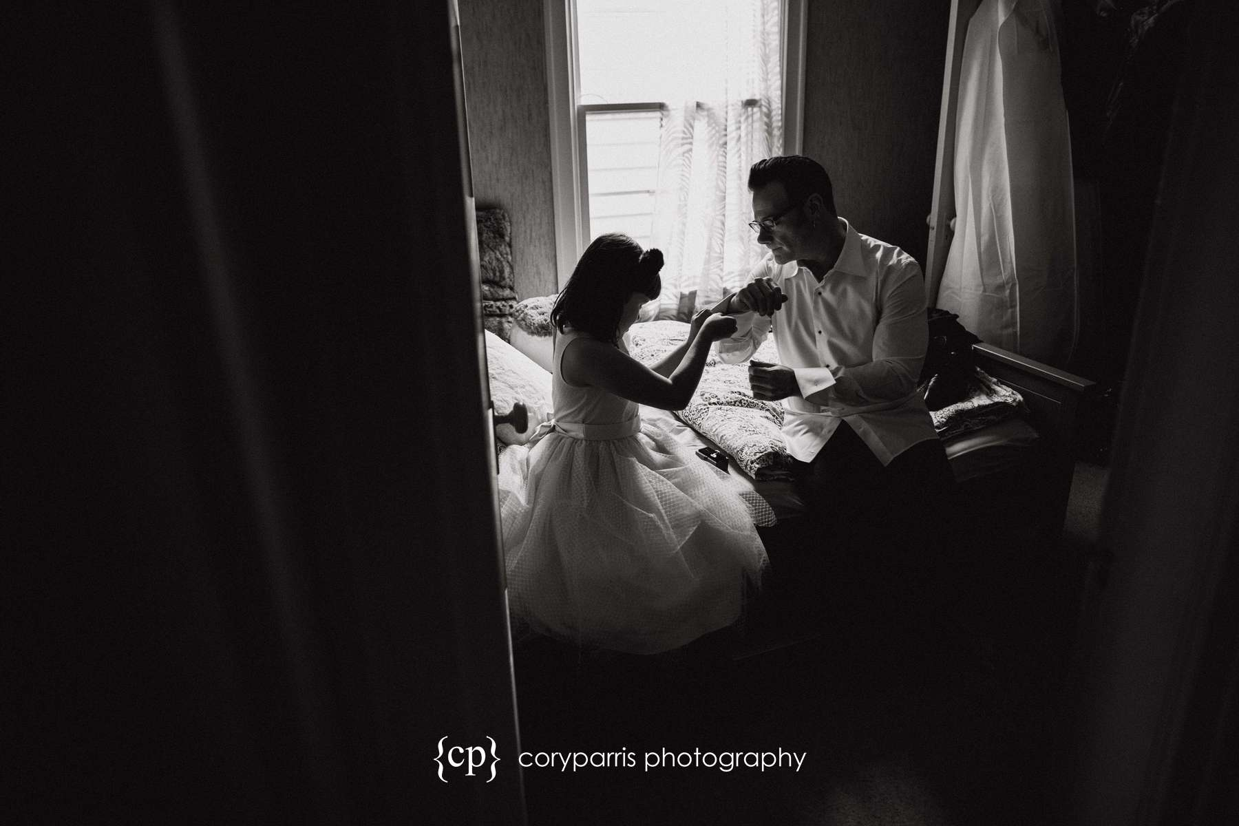 Flower girl helping the groom with his cufflinks.