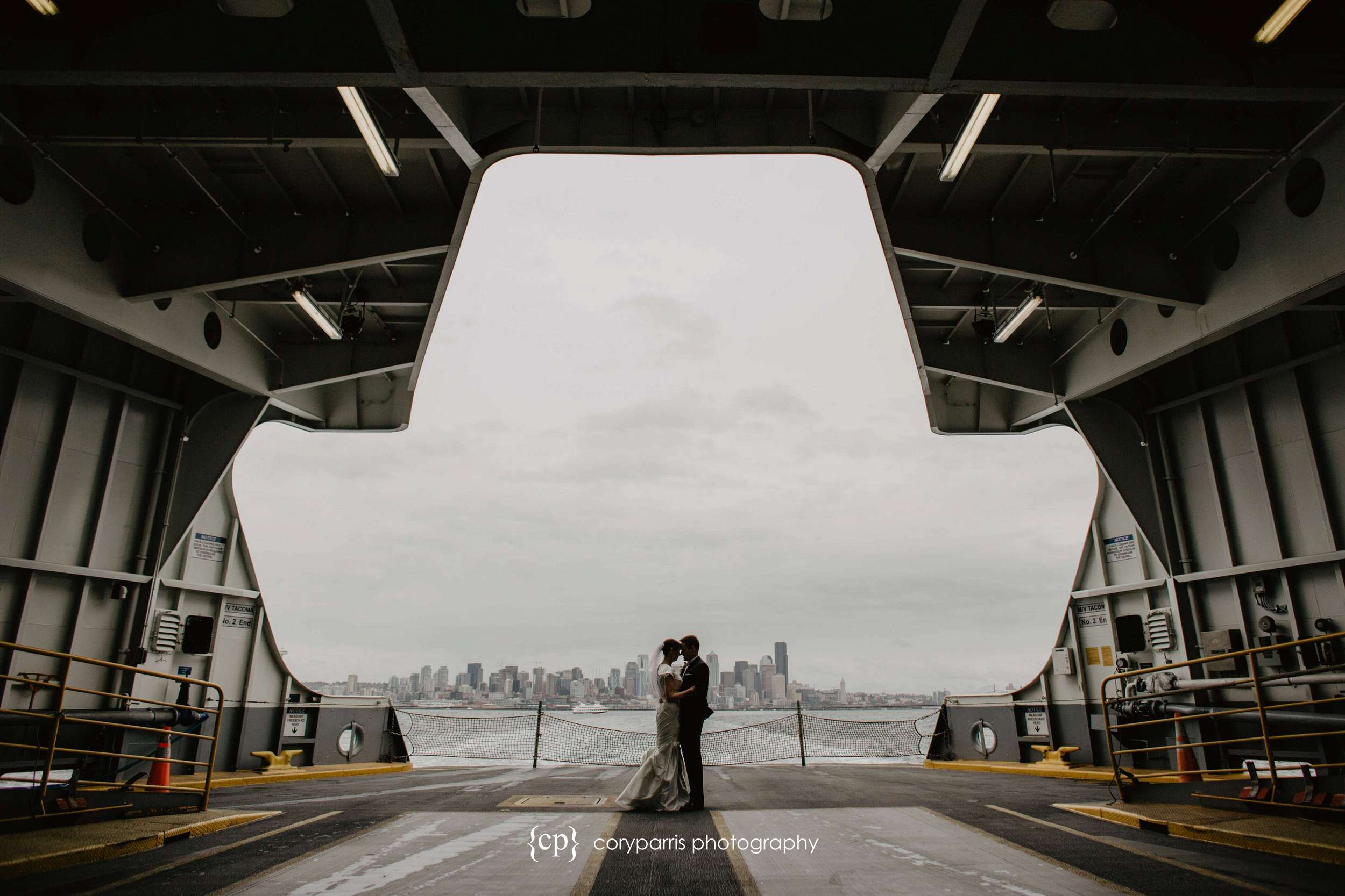 Wedding portrait on the Bainbridge Island Ferry with rainy Seattle behind them. I love spaceship-like shape of the mouth of the ferry.