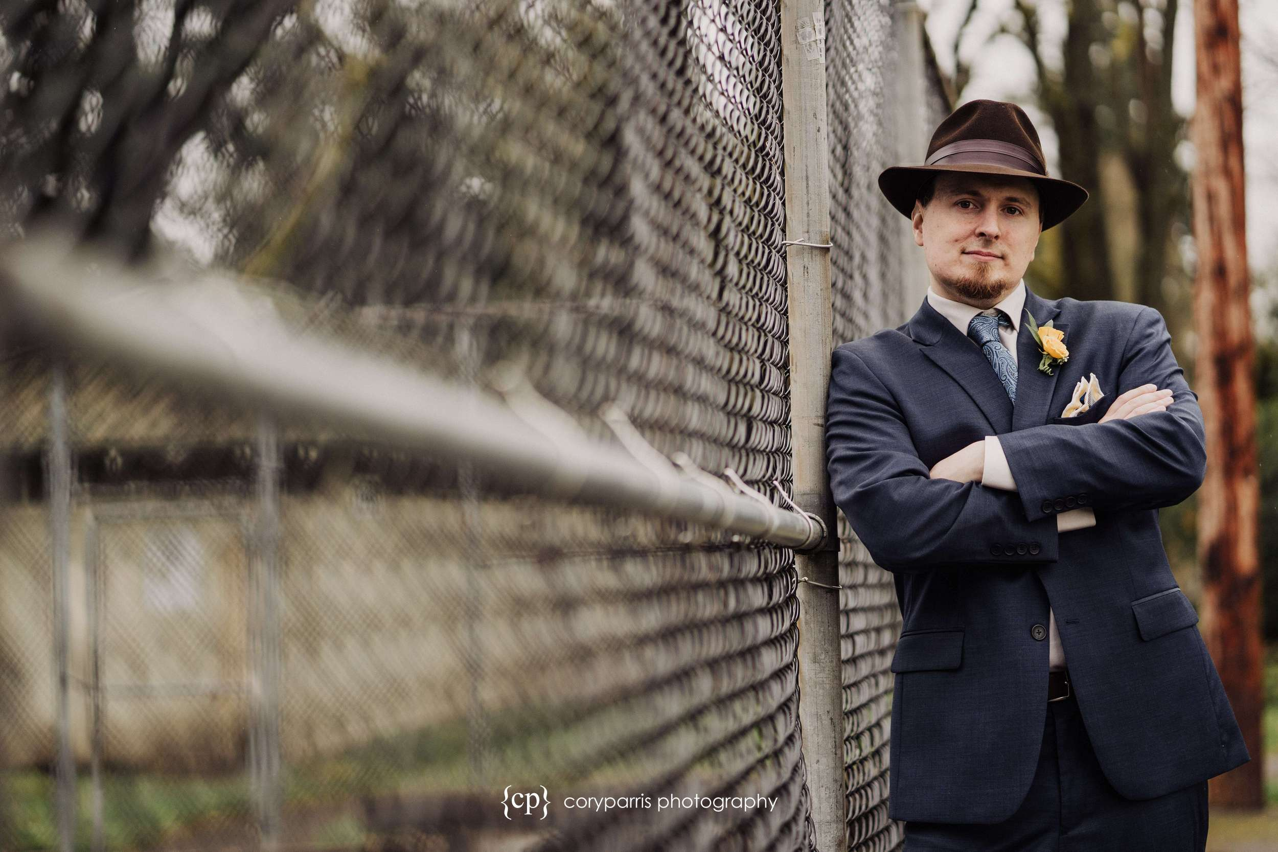 Groom in hat posing next to a fence before everett wedding