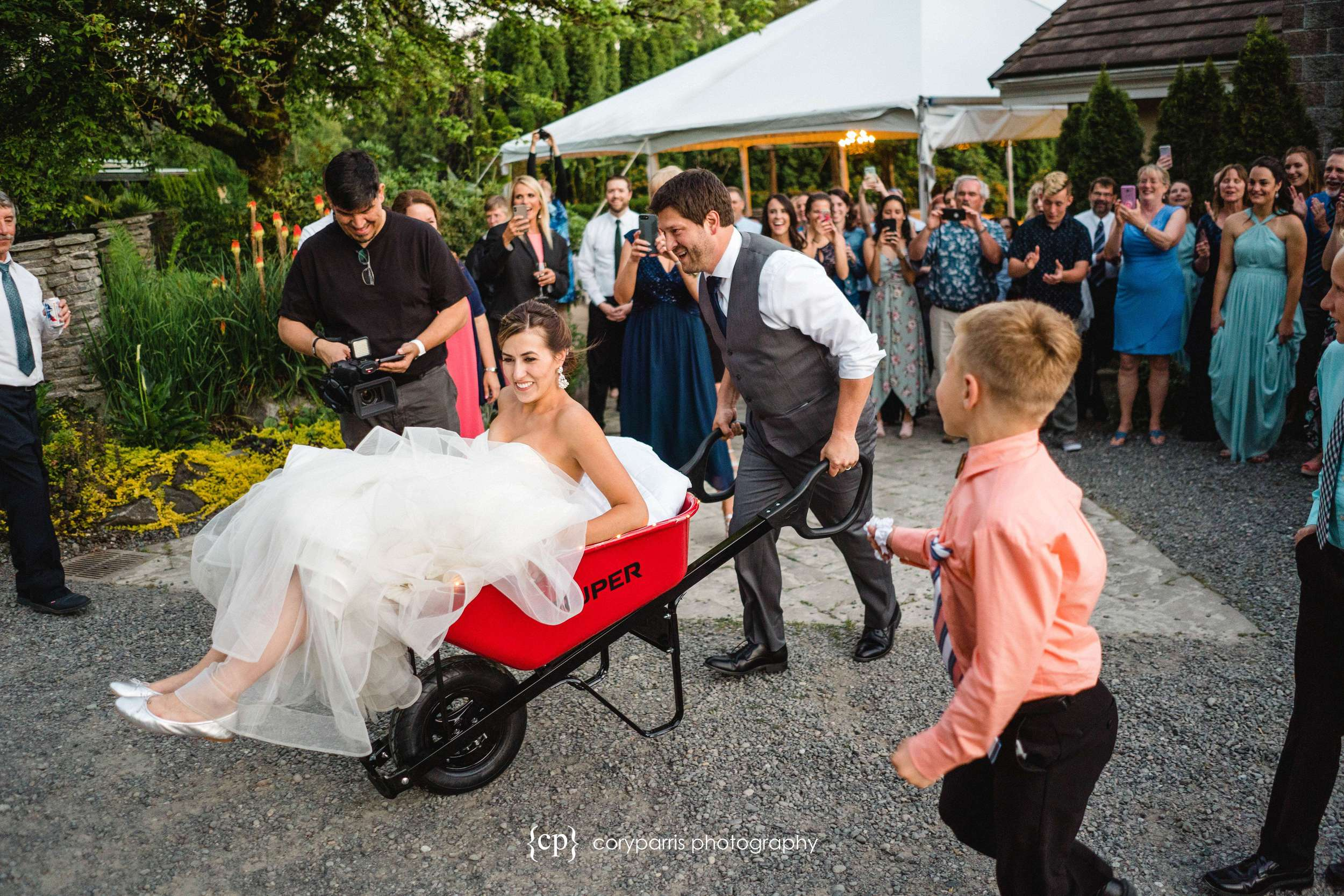 Bride in a wheelbarrow. Evidently a family tradition that I had not heard of before this wedding!