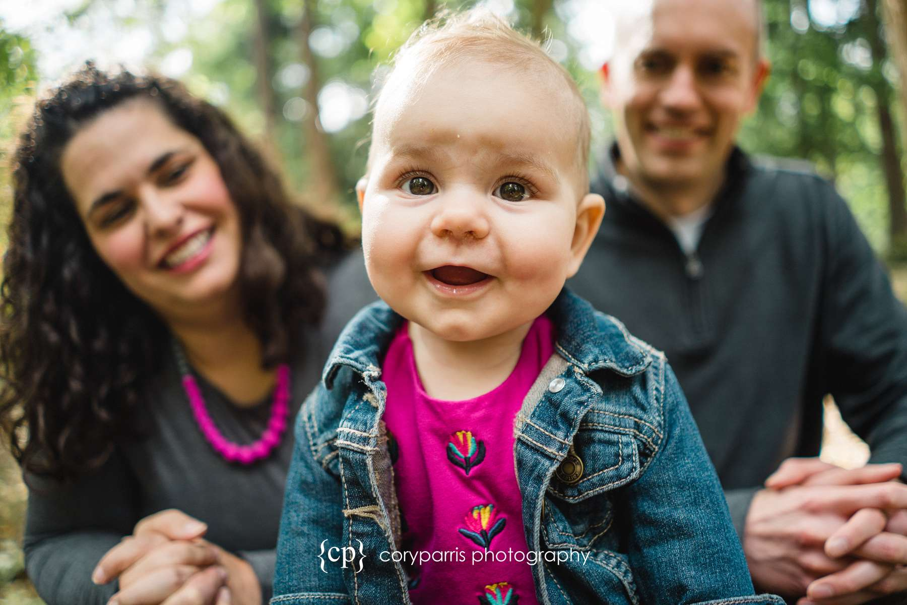 A little girl smiling for the camera in front of her parents at their family portrait session at the Washington Park Arboretum.