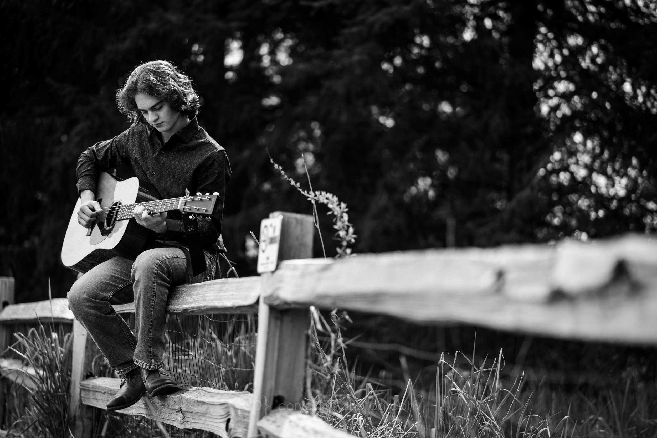 Joshua playing a guitar during his senior portrait session at Marymoor Park in Redmond