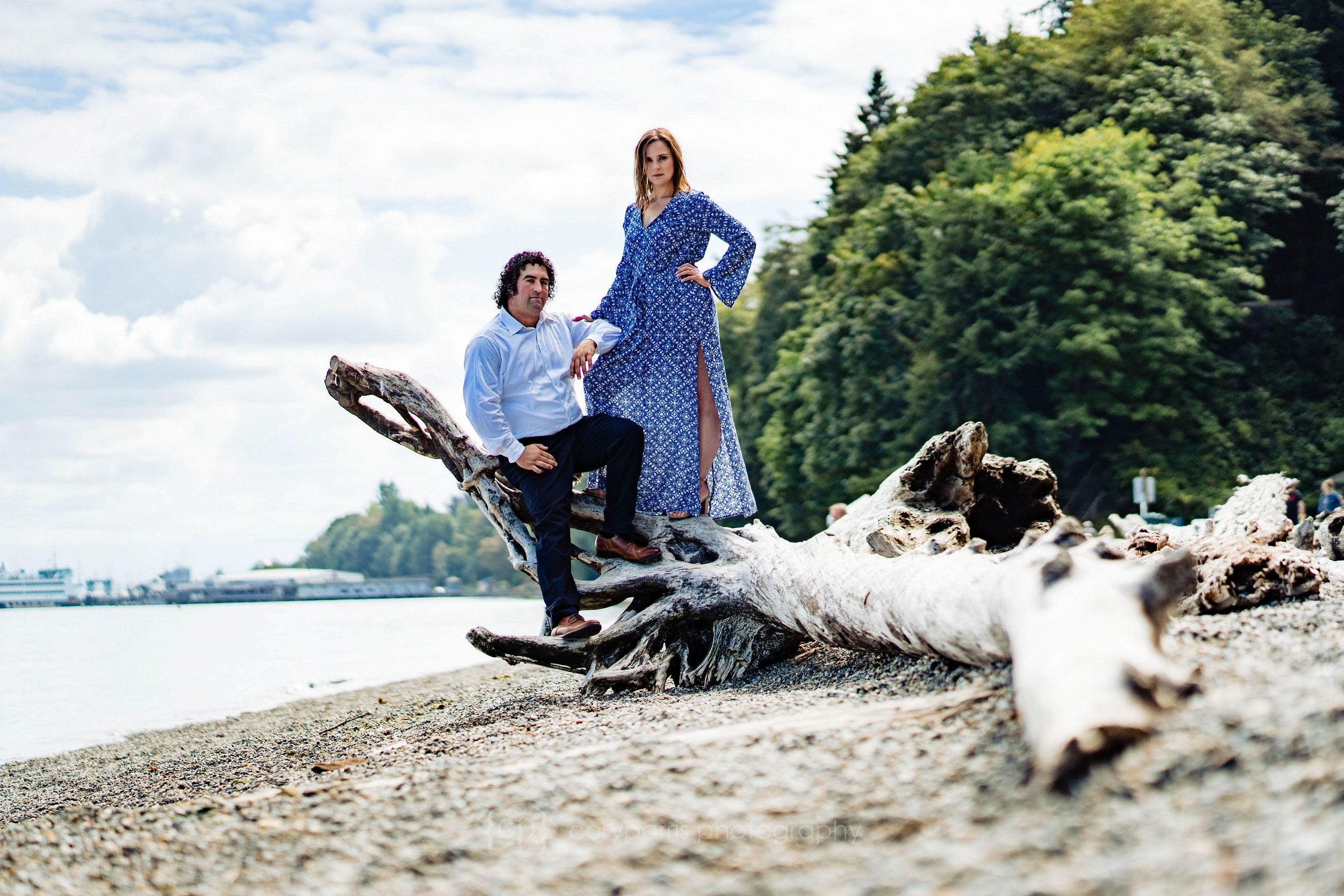 Erin & Adam pose for their engagement portraits on a piece of driftwood at Point Defiance Park in Tacoma.