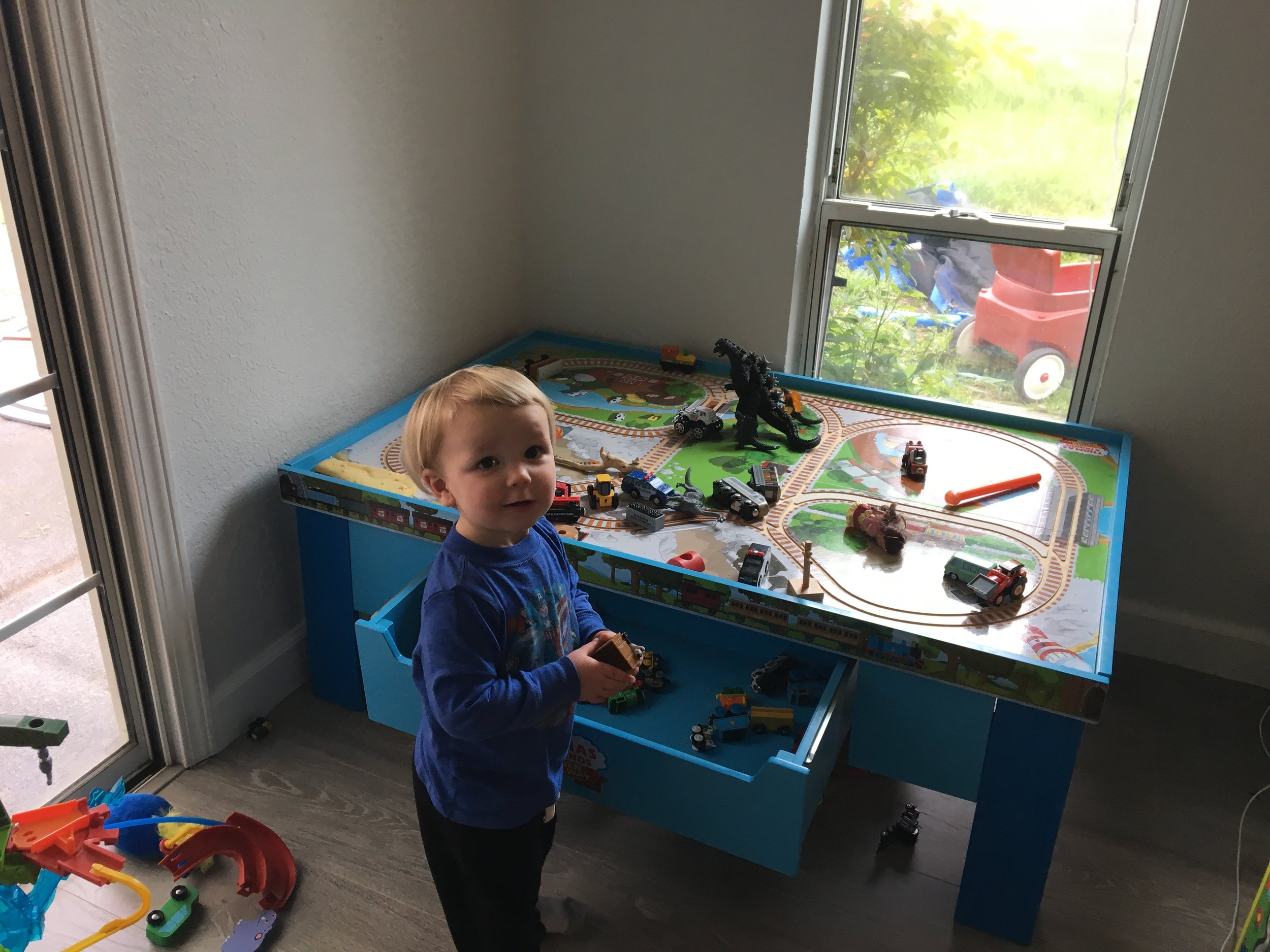 Living his best toddler life -- train table fun at a friend's house