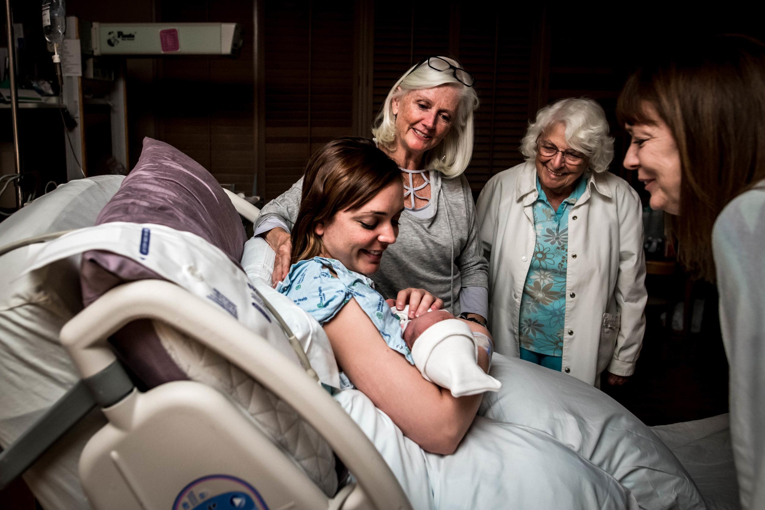generations gather around to see newborn
