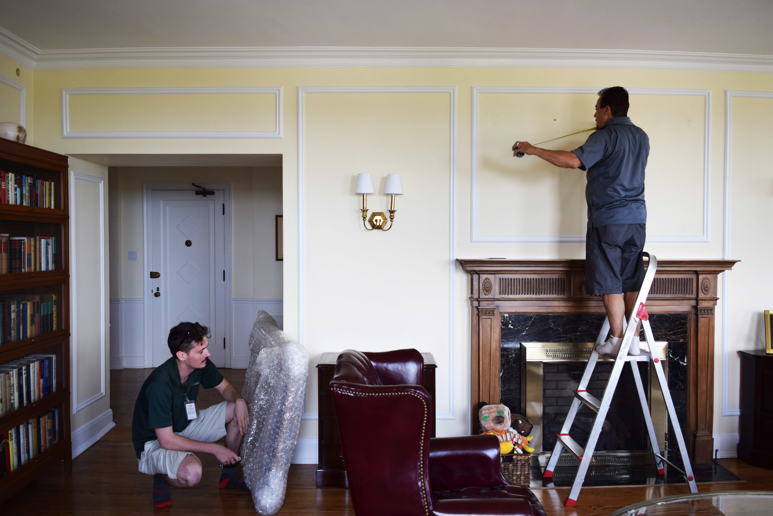 OUR INSTALLERS MEASURE AND PREP THE WALL FOR THE MIRROR. MEASURE TWICE, HAMMER ONCE!