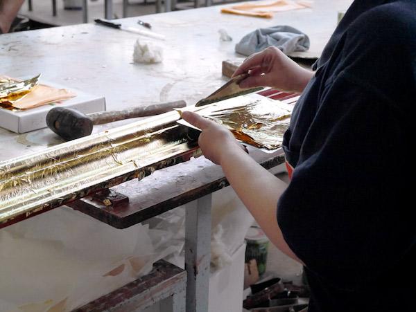 Applying gold leaf by hand.