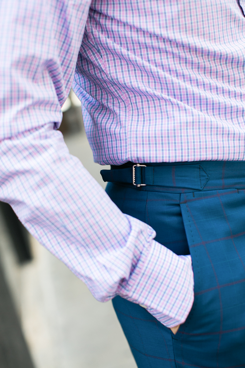 I absolutely love the look of side fasteners on suit trousers.  Side fasteners replace belt-loops which gives the waistband a very clean and dressy look.  And speaking of waistbands, I never wear a belt with my suit trousers.  I prefer the clean look going beltless whether you have belt-loops or not.  For extra style points, wear braces with your suit for a refined look.