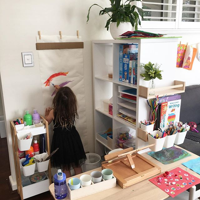 Eve's art space 🌈 so for nearly a year Eve used to have an adult sized desk in the playroom with shelves and all sorts of art & craft things there. She would sit there for ages being allowed to create things of all kinds away from her crawling brother...until he learnt to climb and would dangerously sit on top of the desk or perch on the arm of her chair 😬 the desk got moved. I thought maybe the art thing was a phase (although we have numerous professional artists in our family) but recently I was inspired by some beautiful and brave mummy's @play_at_home_mummy and @storiesofplay who have an open art space for self managed creativity including access to paints 😅 I thought...great, here is my opportunity to follow Eve's interests and see how much independent play/time we can encourage which is something I have learnt so much from @playfullittlelearners . I also wanted to work on following instructions and teaching her to go slower with tasks...she's like me she needs to learn to slow down 😂 so here it is! At this stage jack hasn't shown any interest except for the ant stamper 🤷‍♀️ but he stands there and watches her paint which is cute. She has spent over an hour here every day so far. I was very deliberate with instructions on the first tour...and then we go through them again each morning before she goes in and sets herself up 😍 She has learnt to: 👩🏻‍🎨 plaint slowly near the edges of the paper 🌈 pour her own paints into the cups 💦 wash and dry her brushes at the end of the day ✨ pack away any excess glitter, sparkles, feathers or Pom poms into their boxes and put them back on the shelf. I've also added a little bin that once she's wiped down her desk she puts any rubbish in 🙌🏻 I got the wall easel idea from Emma at @play_at_home_mummy 💕