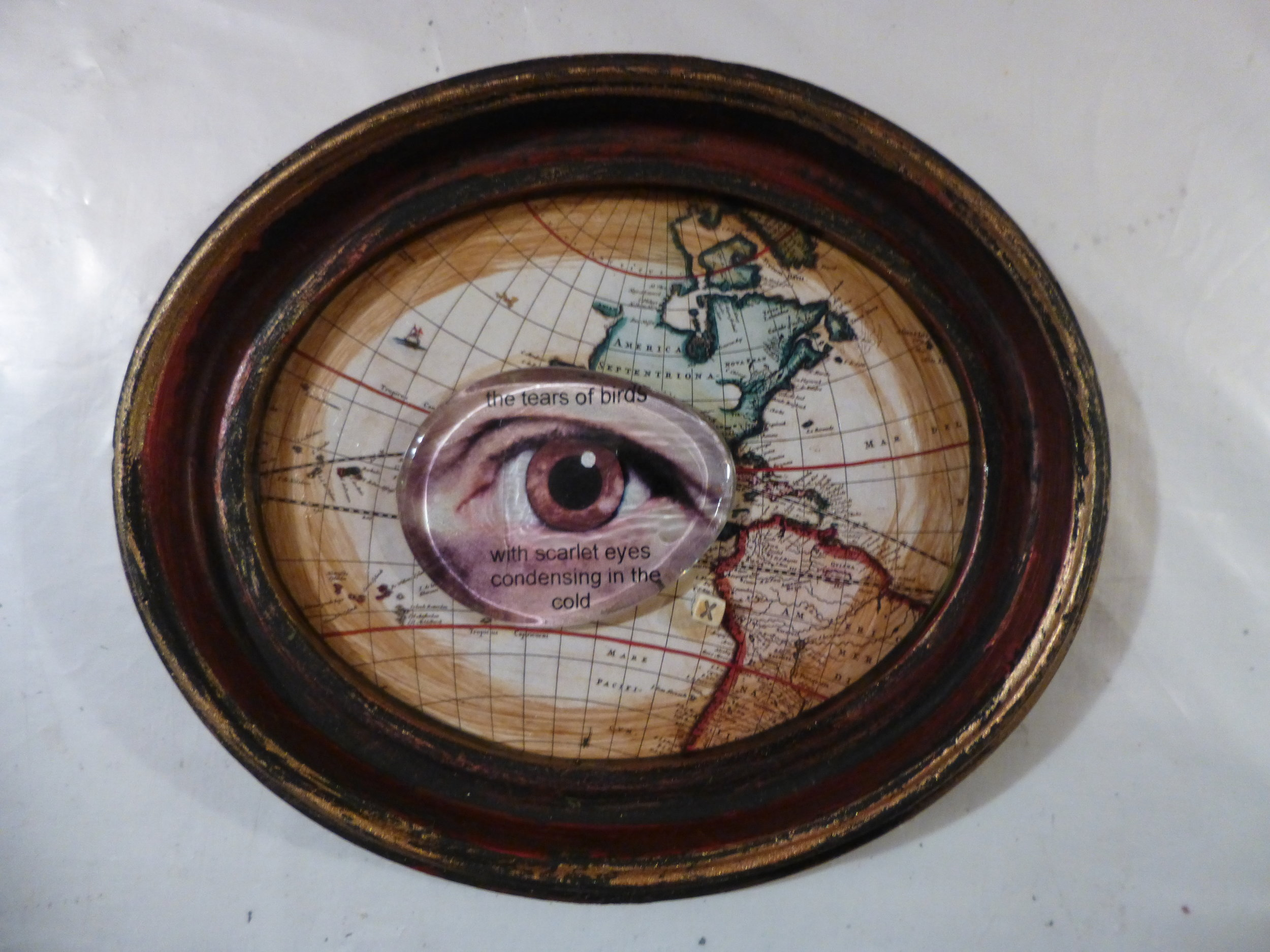 Mixed media collage. Small oval recycled frame from the thrift shop, glass glob, photograph of my eye, old map from a calendar, paint.