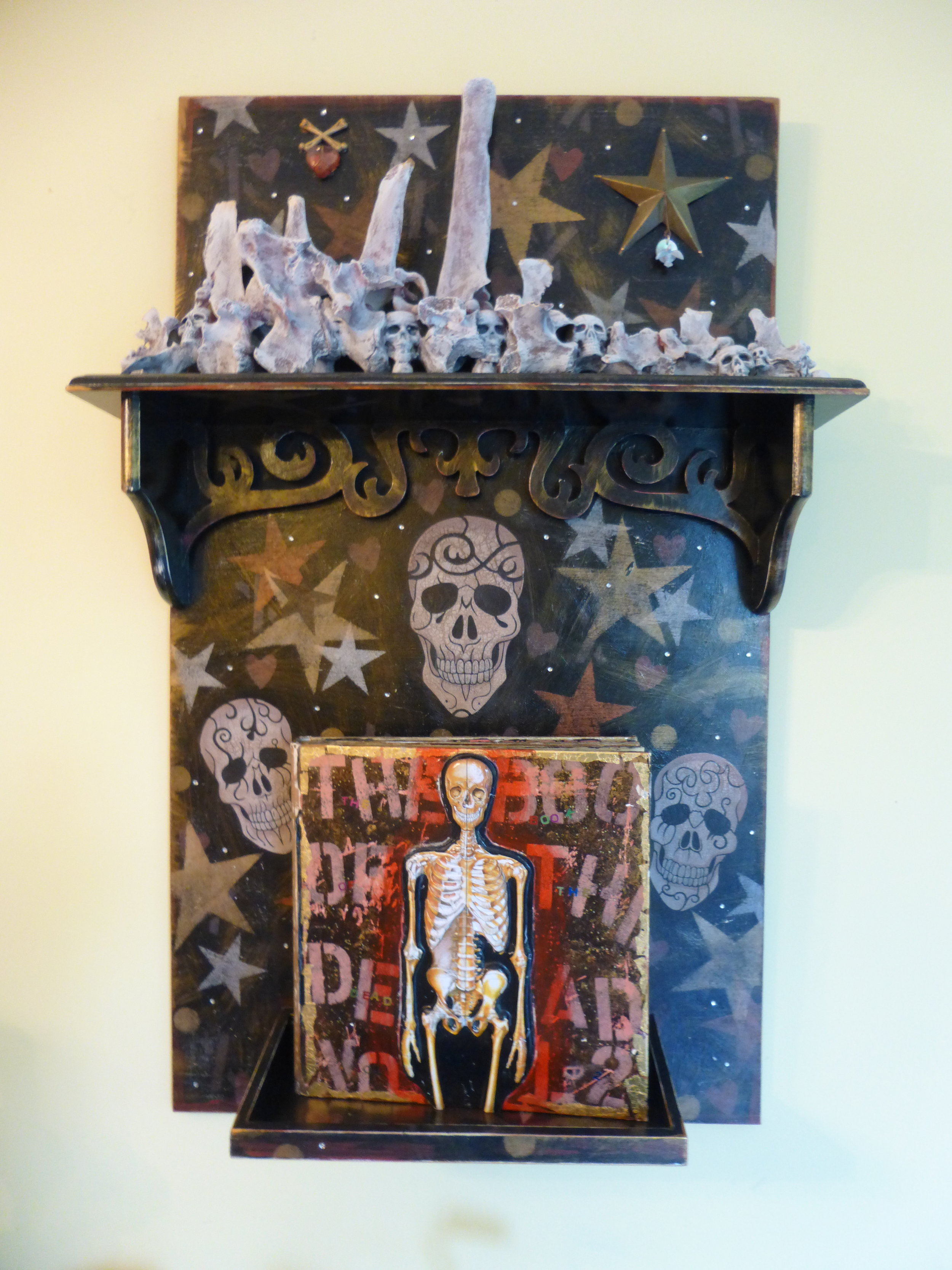 """the book of the dead - volume 2"", mixed-media collage.  Wood, moose vertebrae, plastic skulls, skeleton from the dollar store, acrylic paint, book, text."