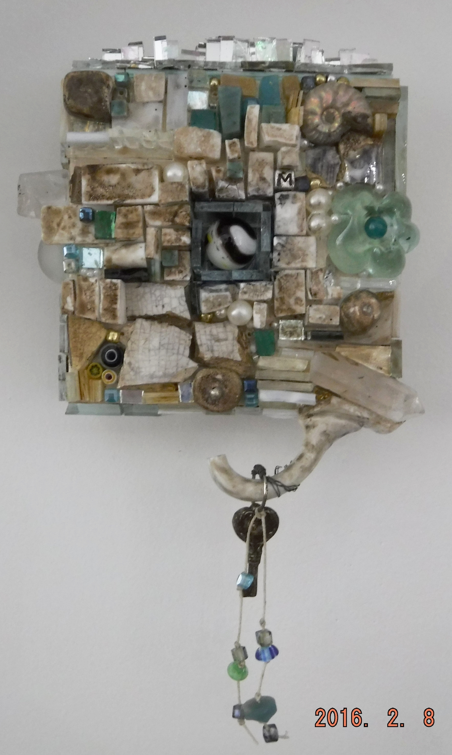 Glass mosaic in wooden shadow box, glass, beads, found objects, pottery, waxed thread, ammonite.