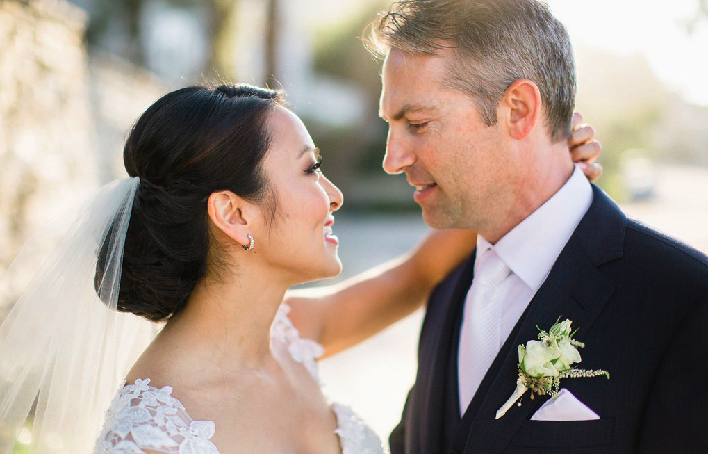 Asian Bride with Updo Hairstyle and Veil Looking Into Husband's Eyes in Wedding Photos. Bridal Hair and Makeup by Vanity Belle in Orange County (Costa Mesa) and San Diego (La Jolla)