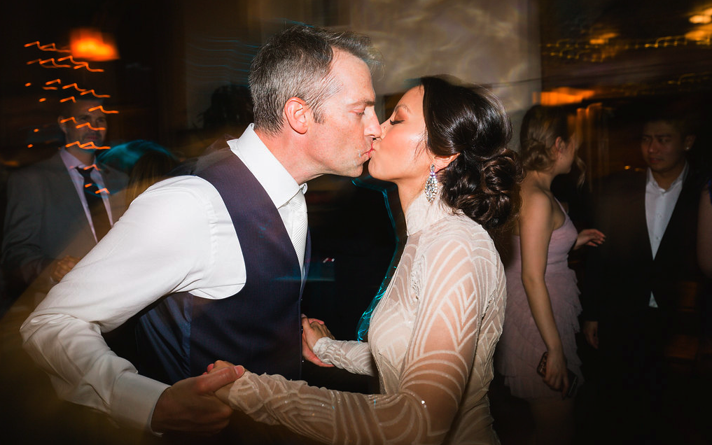 Wedding reception photos with bride and husband kissing. Bridal Hair and Makeup by Vanity Belle in Orange County (Costa Mesa) and San Diego (La Jolla)